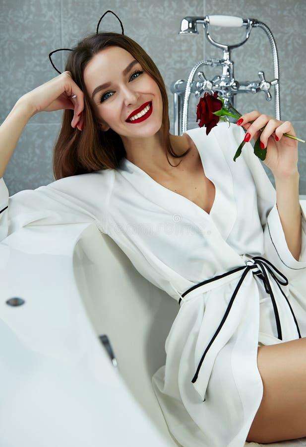 Mulher 'sexy' no banheiro no dia de Valentim cor-de-rosa da veste de seda imagens de stock royalty free