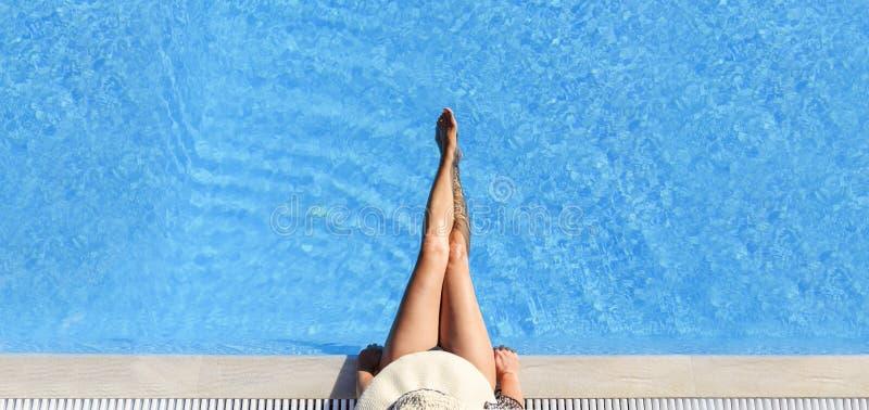 Mulher 'sexy' no biquini e sunhat que relaxa na piscina imagens de stock