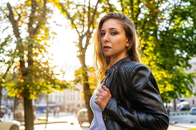 Mulher 'sexy' no casaco de cabedal preto na rua com sol do luminoso Fotografia da forma da rua foto de stock royalty free