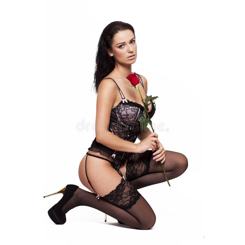 A mulher 'sexy' no espartilho e as meias que ajoelham-se com aumentaram fotos de stock royalty free