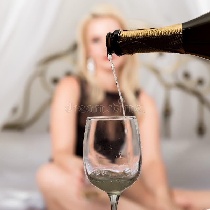 Mulher 'sexy' no roupa interior em uma cama que espera seu amante Foco no vidro do champanhe Datando o conceito fotos de stock