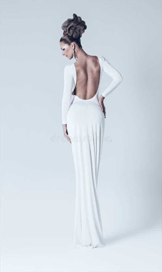 Mulher 'sexy' no vestido branco com parte traseira despida imagens de stock