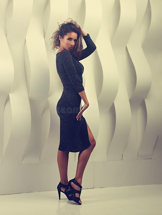 Mulher 'sexy' no vestido cinzento da forma que levanta perto do wal branco de papel foto de stock royalty free