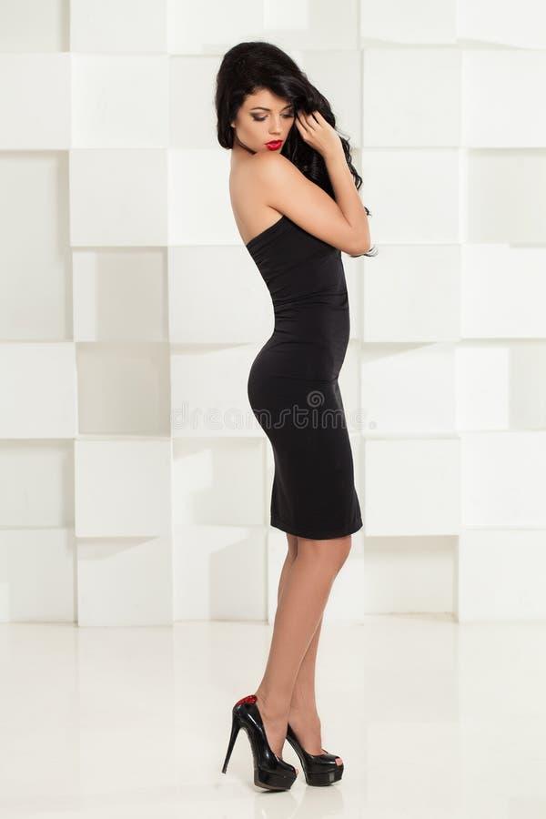 Mulher 'sexy' no vestido de cocktail e em sapatas pretos dos saltos altos imagem de stock