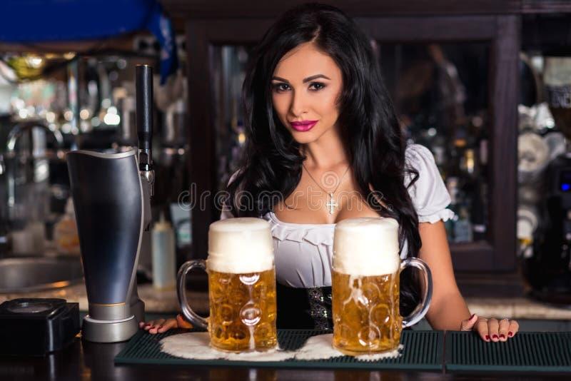 Mulher 'sexy' no vestido do dirndl que guarda o caneco de cerveja da cerveja de Oktoberfest foto de stock royalty free