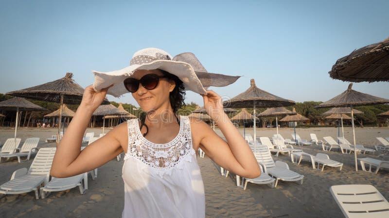 Mulher 'sexy' no vestido e no chapéu brancos que anda na praia vazia imagens de stock royalty free