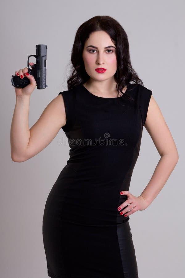 Mulher 'sexy' no vestido preto que guarda a arma sobre o cinza imagem de stock