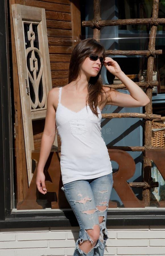 Mulher 'sexy' nos óculos de sol fora da loja antiga fotografia de stock royalty free