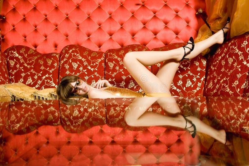 Mulher 'sexy' nos vidros que colocam no sofá fotografia de stock