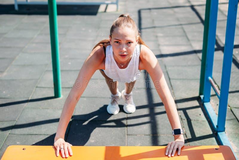Mulher 'sexy' nova desportiva que faz impulso-UPS do banco no campo de esportes Estilo de vida saudável do conceito foto de stock royalty free