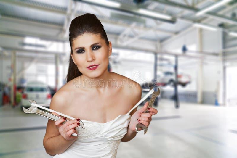 Mulher 'sexy' nova em um vestido branco guardando wrenchs em seus braços fotos de stock