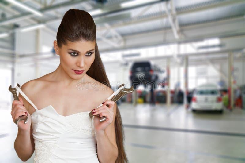 Mulher 'sexy' nova em um vestido branco guardando wrenchs em seus braços foto de stock royalty free
