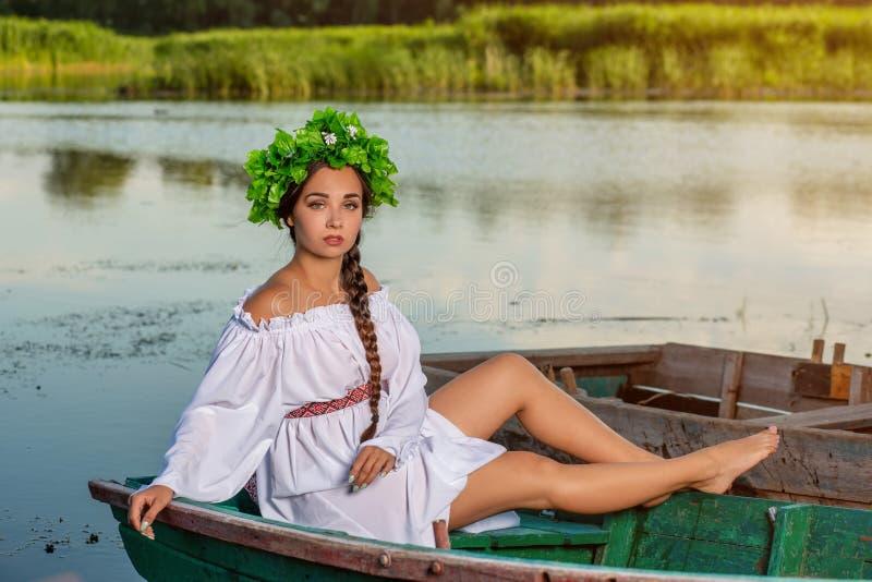 Mulher 'sexy' nova no barco no por do sol A menina tem uma grinalda da flor em sua cabeça, relaxando e navegando no rio Terra e r fotos de stock royalty free