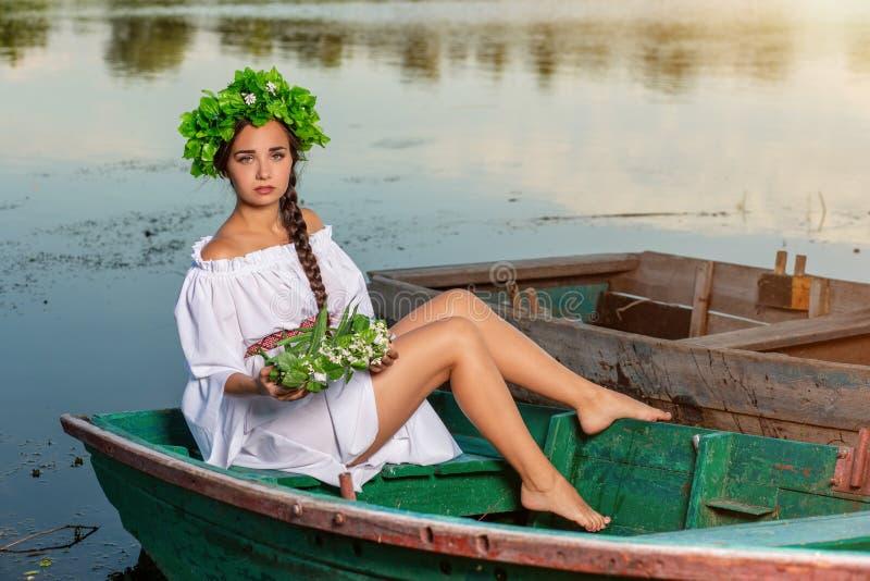 Mulher 'sexy' nova no barco no por do sol A menina tem uma grinalda da flor em sua cabeça, relaxando e navegando no rio Terra e r foto de stock