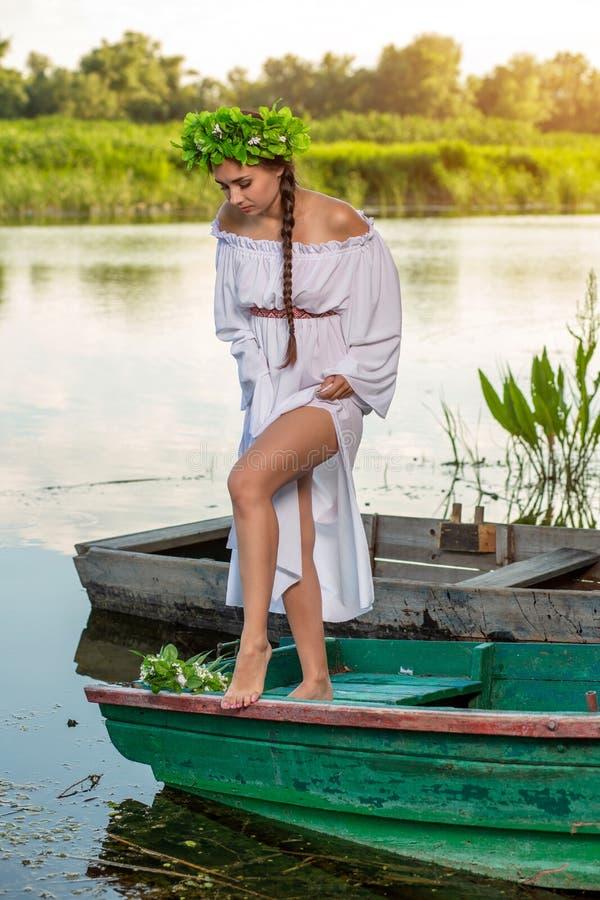Mulher 'sexy' nova no barco no por do sol A menina tem uma grinalda da flor em sua cabeça, relaxando e navegando no rio Terra e r imagens de stock