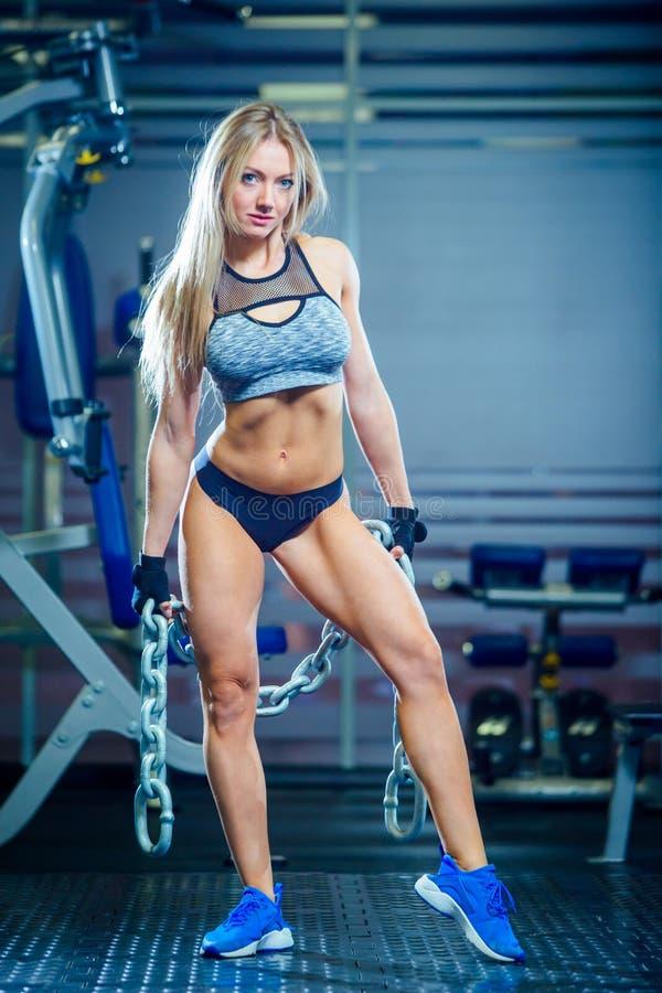 Mulher 'sexy' nova que faz exercícios com a corrente pesada no gym Halterofilismo clássico Fazer louro muscular da mulher da apti imagens de stock royalty free