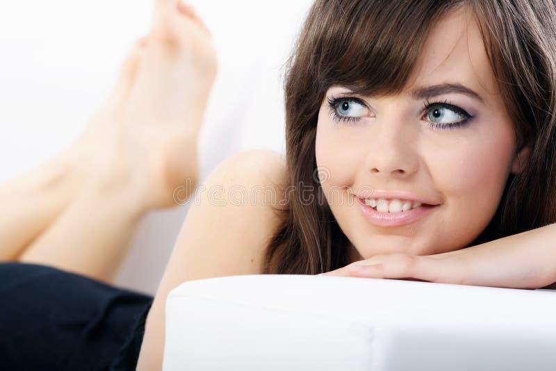 Mulher 'sexy' nova que relaxa em um sofá imagem de stock