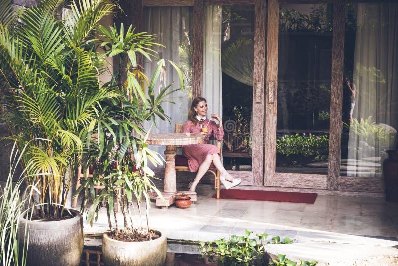 Mulher 'sexy' nova que siiting na cadeira em sua casa de campo luxuosa Ilha de Bali imagem de stock