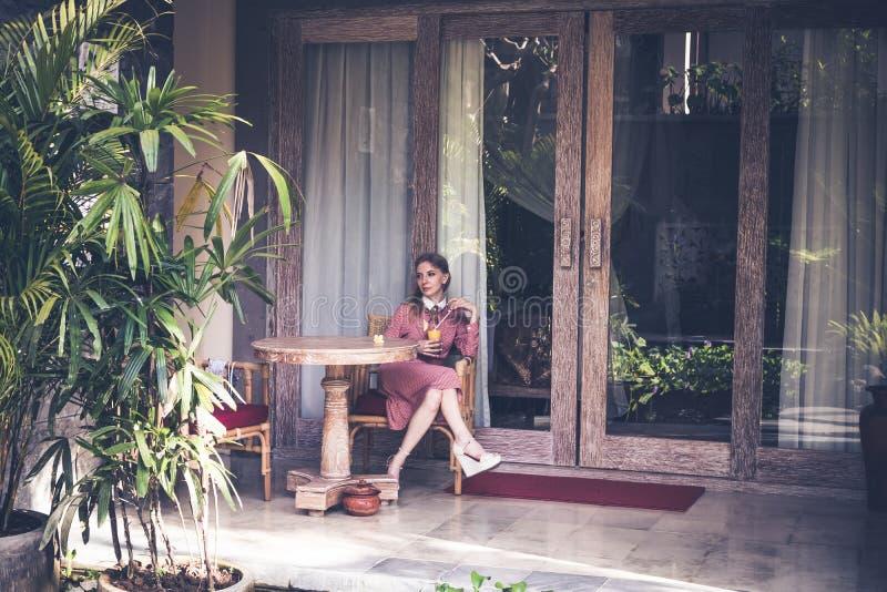 Mulher 'sexy' nova que siiting na cadeira em sua casa de campo luxuosa Ilha de Bali fotografia de stock royalty free