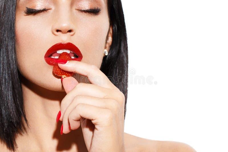 Mulher 'sexy' que come a morango isolada no branco imagens de stock royalty free