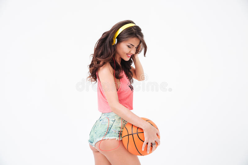 Mulher 'sexy' que guarda a bola do basquetebol e a música de escuta nos fones de ouvido fotografia de stock royalty free