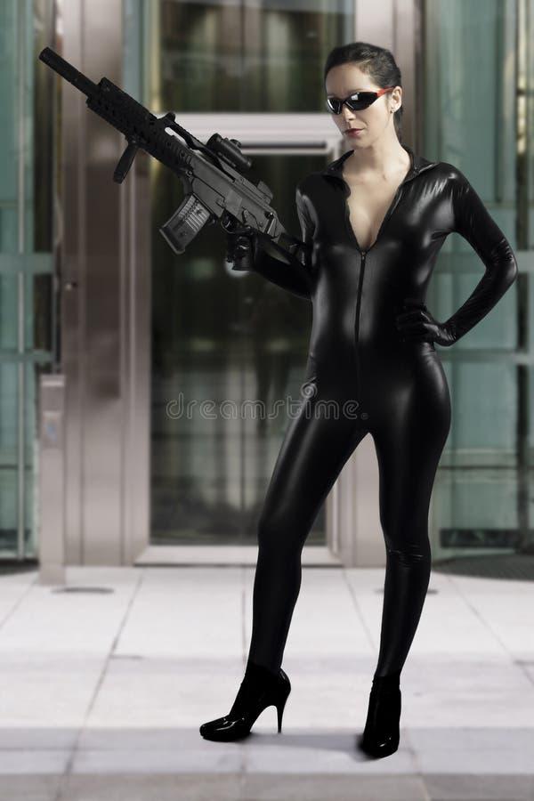 Mulher 'sexy' que guardara a arma que veste um vestido de couro preto imagens de stock royalty free