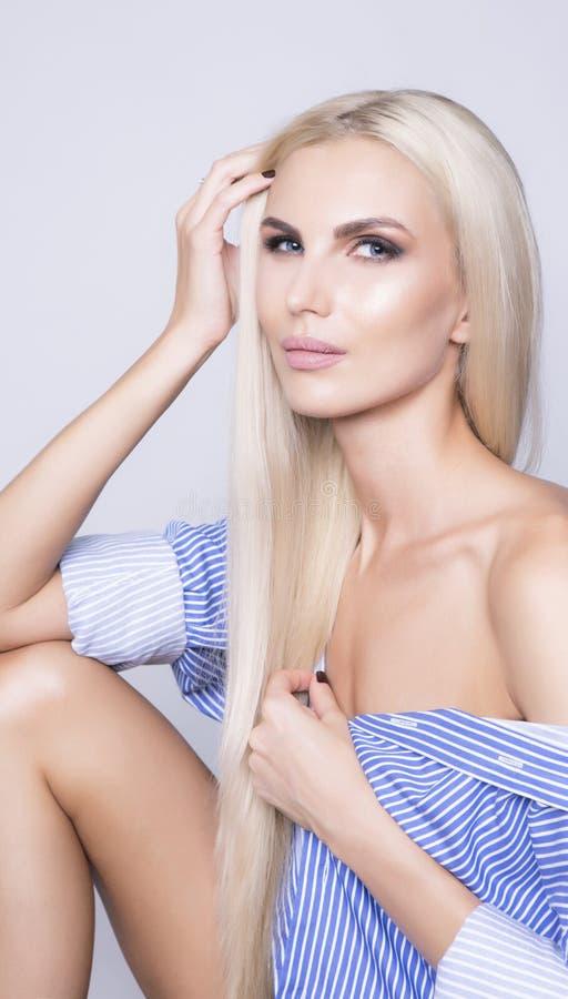 Mulher 'sexy' que senta-se na camisa do negócio Cabelo louro da platina longa fotografia de stock royalty free