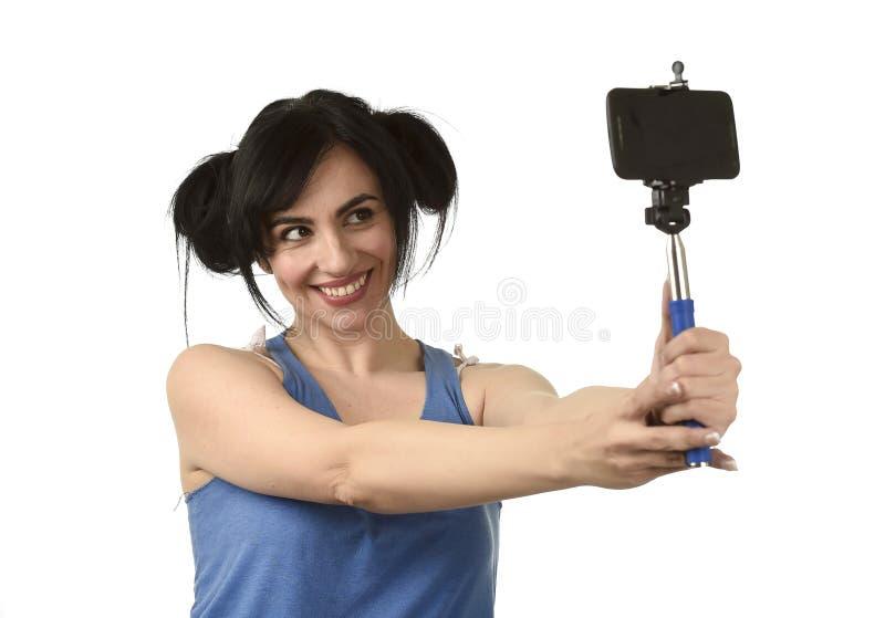 Mulher 'sexy' que toma a foto do selfie com o levantamento da câmera da vara e do telefone celular feliz imagem de stock
