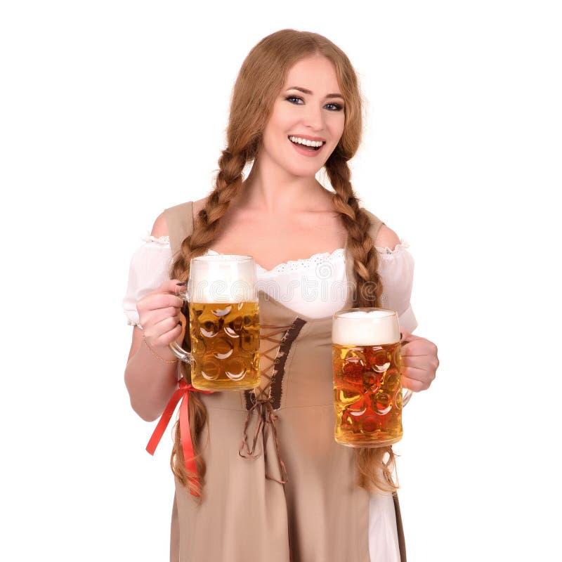 Mulher 'sexy' que veste um dirndl com as duas canecas de cerveja sobre o branco foto de stock