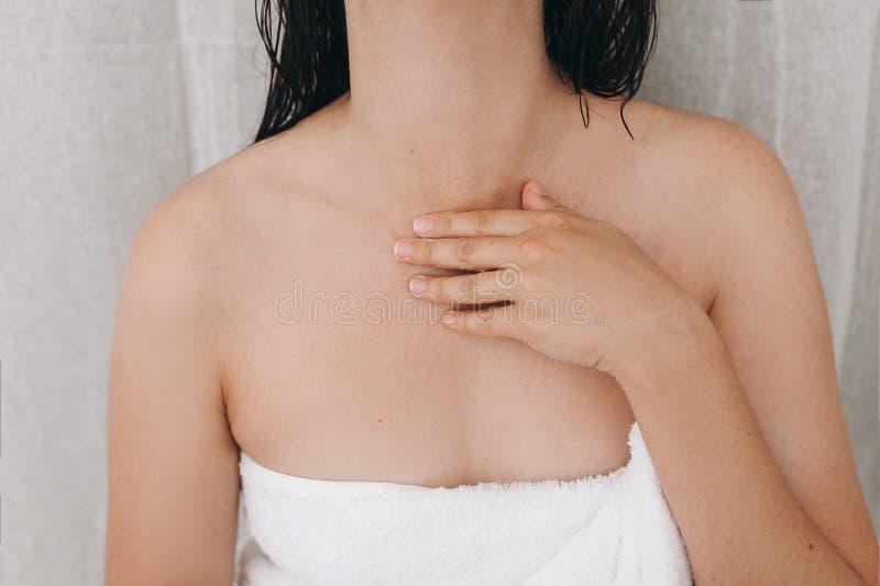 Mulher 'sexy' relaxado na toalha branca que aplica o creme hidratando no pescoço no banheiro, close up Cuidado da pele e do corpo imagens de stock royalty free