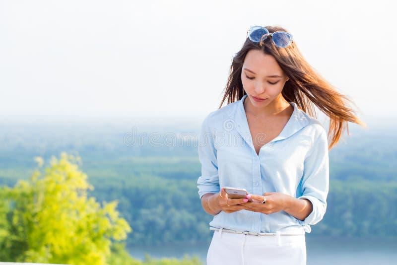 Mulher 'sexy' sensual bonita com smartphone disponível na natureza Tecnologia moderna, curso, verão, estilo de vida fotos de stock