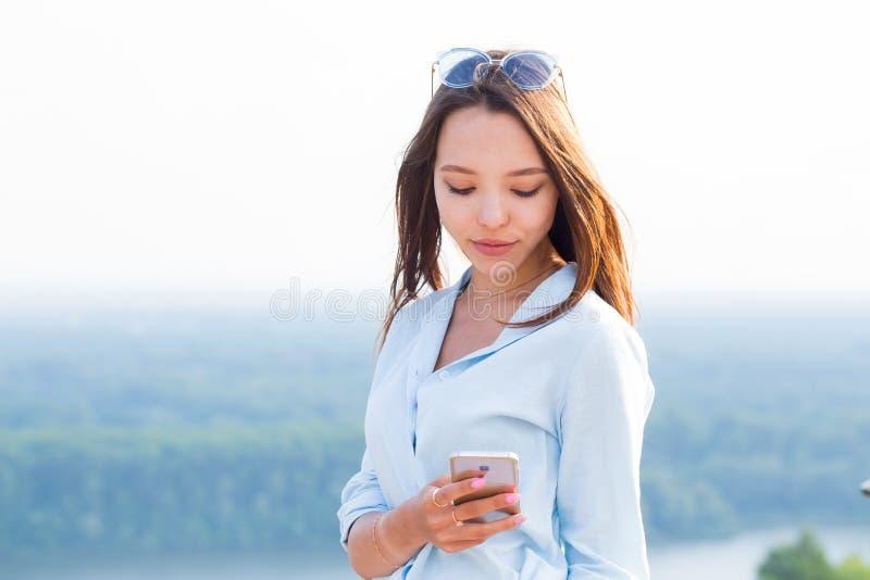 Mulher 'sexy' sensual bonita com smartphone disponível na natureza Tecnologia moderna, curso, verão, estilo de vida imagens de stock royalty free
