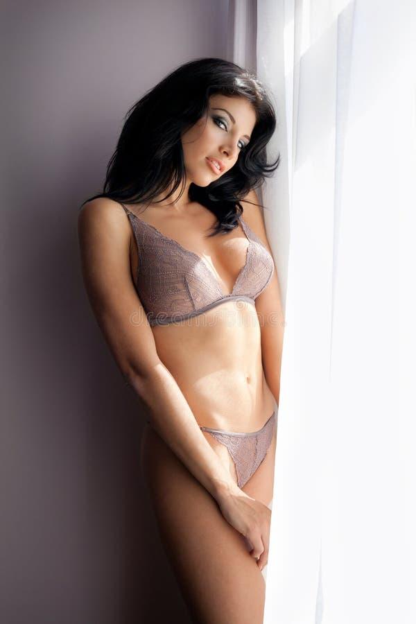 Mulher  Sexy  Sensual Que Levanta Na Roupa Interior Perto Do Indicador Fotos de Stock Royalty Free