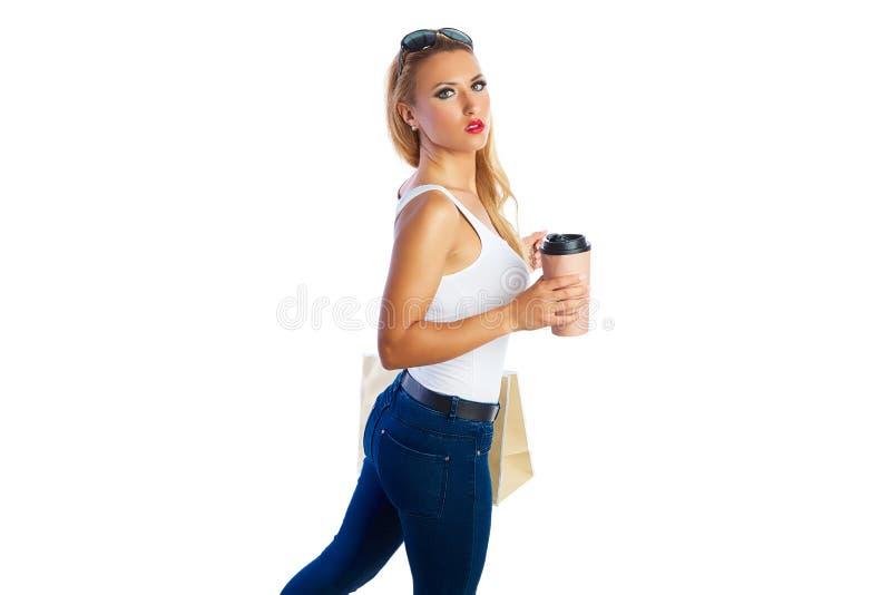 A mulher shopaholic loura ensaca o fundo branco foto de stock