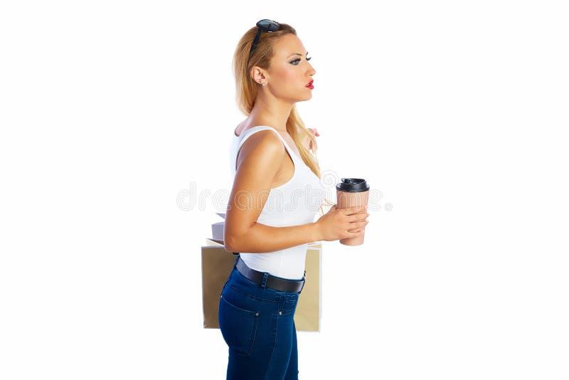 A mulher shopaholic loura ensaca o fundo branco fotografia de stock