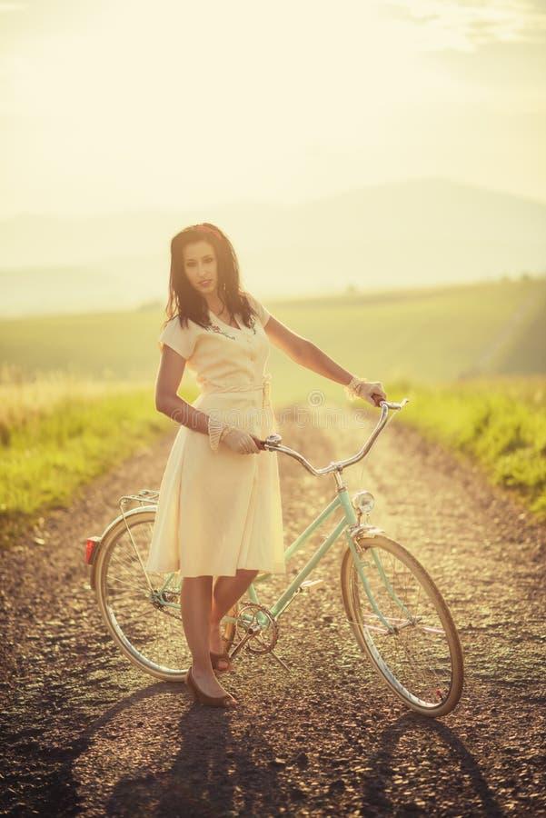 Mulher smilling consideravelmente nova com a bicicleta retro no por do sol na estrada, tempos velhos do vintage, menina no estilo fotos de stock
