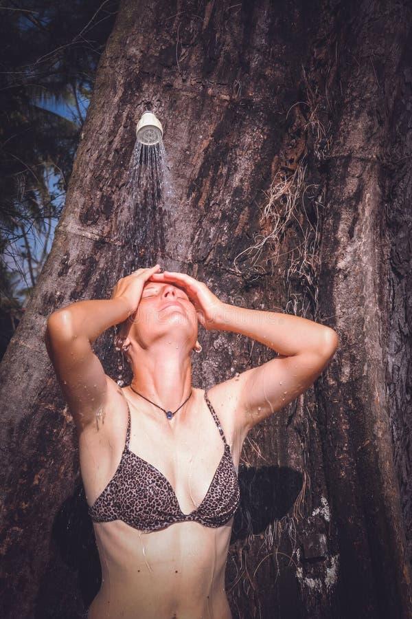 Mulher sob o chuveiro tropical fotografia de stock royalty free