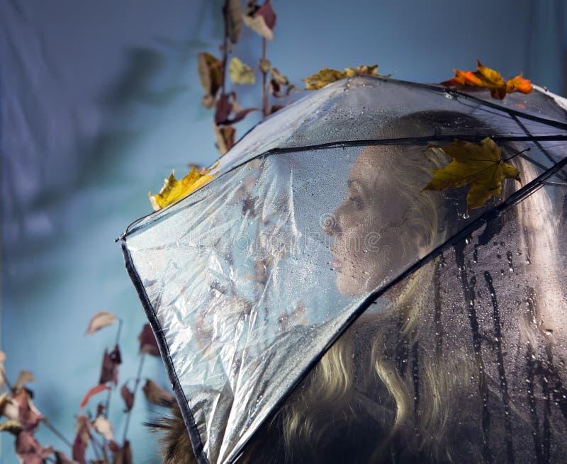 Mulher sob um guarda-chuva transparente com folhas de outono fotos de stock royalty free