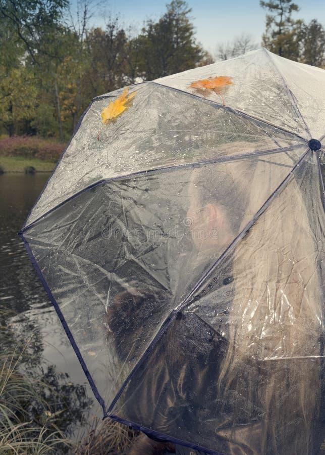 Mulher sob um guarda-chuva transparente em um dia nebuloso do outono na costa do lago imagens de stock royalty free