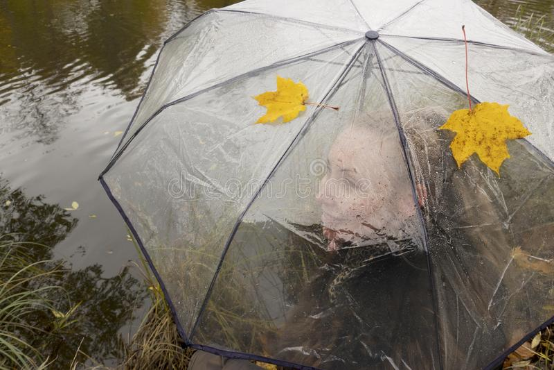 Mulher sob um guarda-chuva transparente em um dia nebuloso do outono na costa do lago imagem de stock royalty free