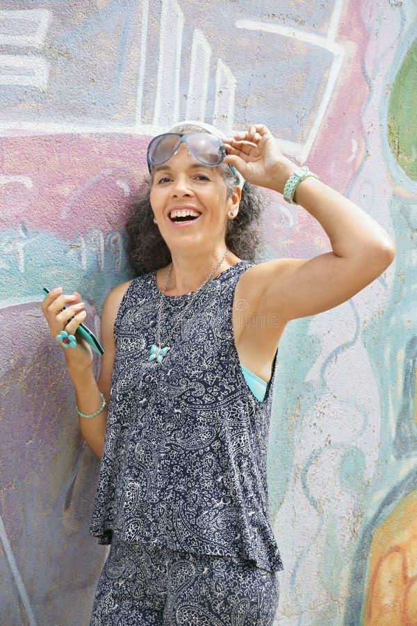 A mulher sobre 50 com grafittis do smartphone mura o fundo fotos de stock royalty free