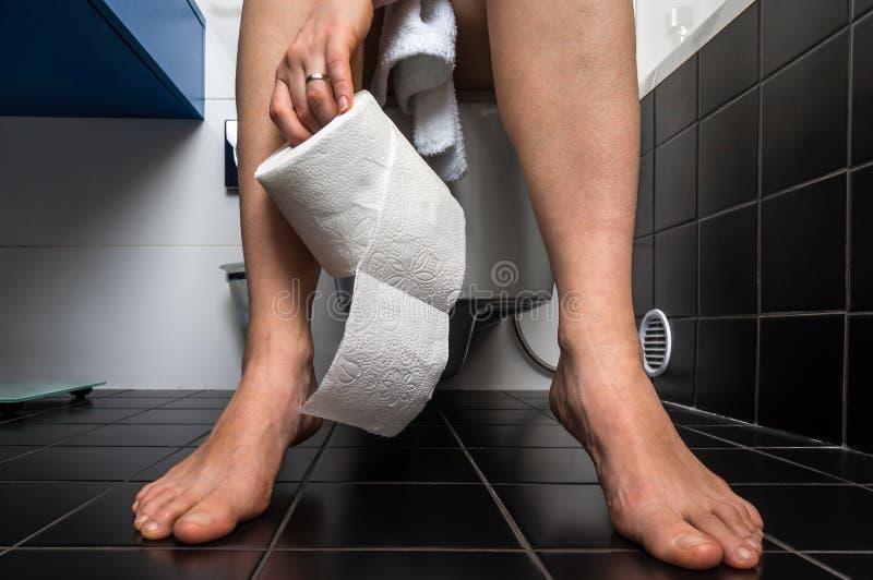 A mulher sofre da diarreia está sentando-se na bacia de toalete imagens de stock