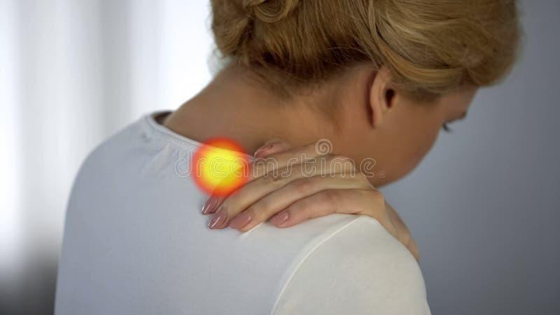 A mulher sofre da dor do ombro, osteodistrofia, ponto indica a dor de músculo fotos de stock