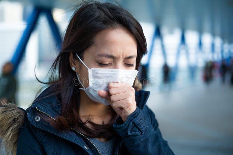 A mulher sofre da tosse com proteção da máscara protetora fotografia de stock