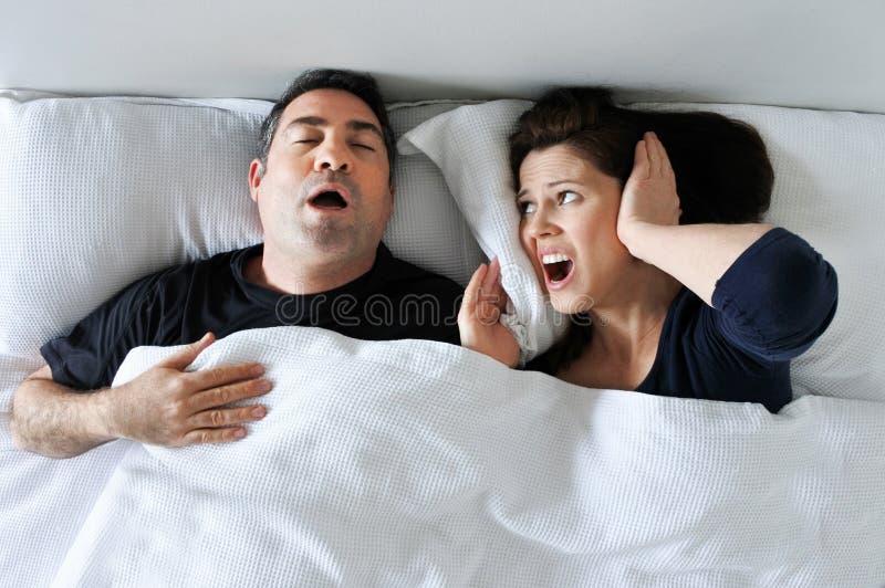 A mulher sofre de seu sócio que ressona na cama imagens de stock