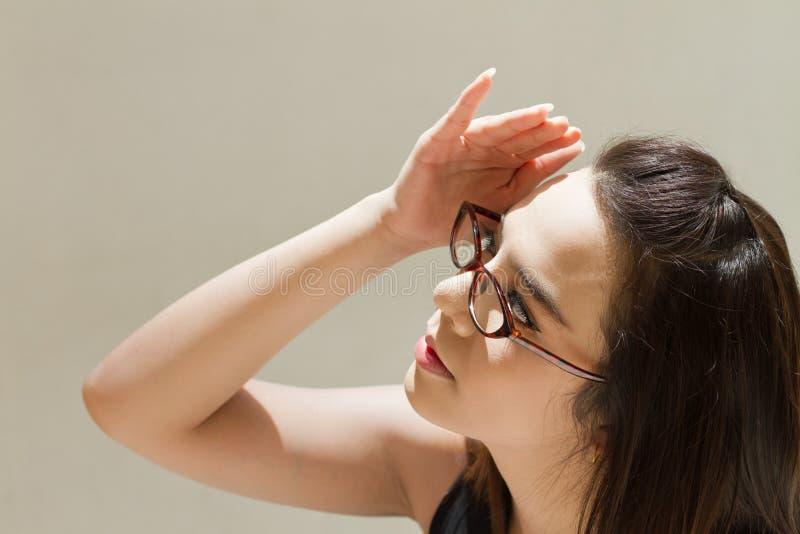 A mulher sofre do calor da luz solar forte fotografia de stock