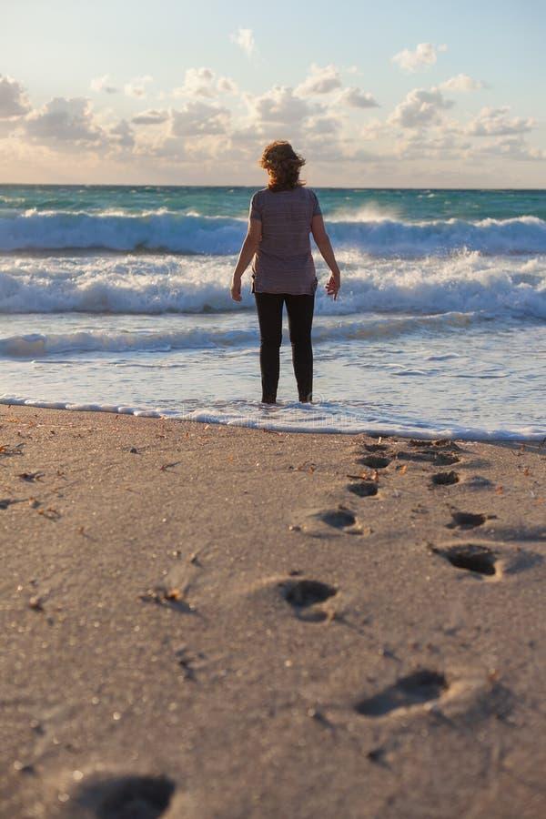 Mulher solitária que está na praia no sol de ajuste imagem de stock