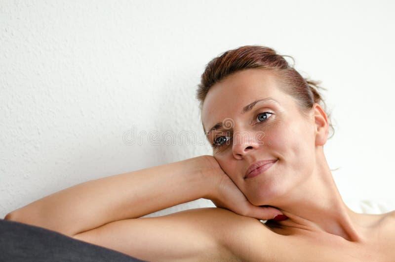 Mulher sonhadora atrativa que relaxa em um sofá fotografia de stock