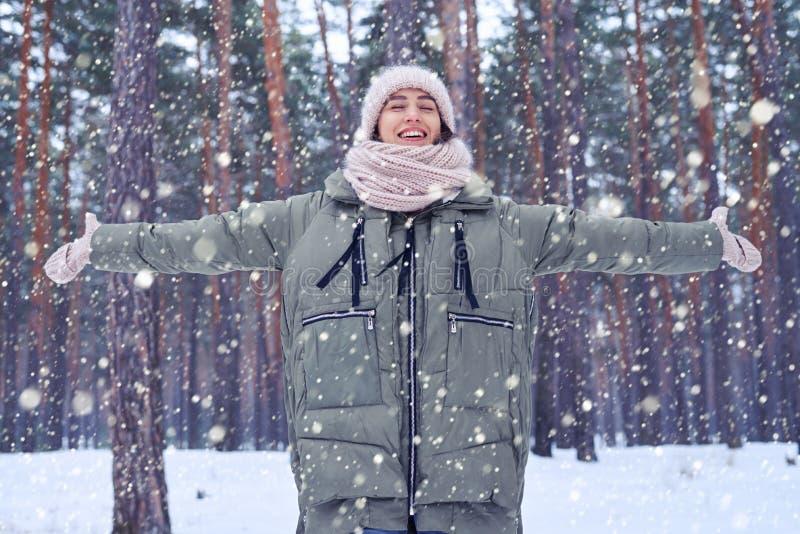 Mulher sonhadora com os olhos fechados que travam a neve de queda com estiramento fotografia de stock
