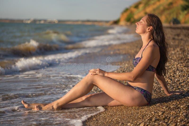 A mulher sonhadora senta-se na ressaca do mar fotografia de stock